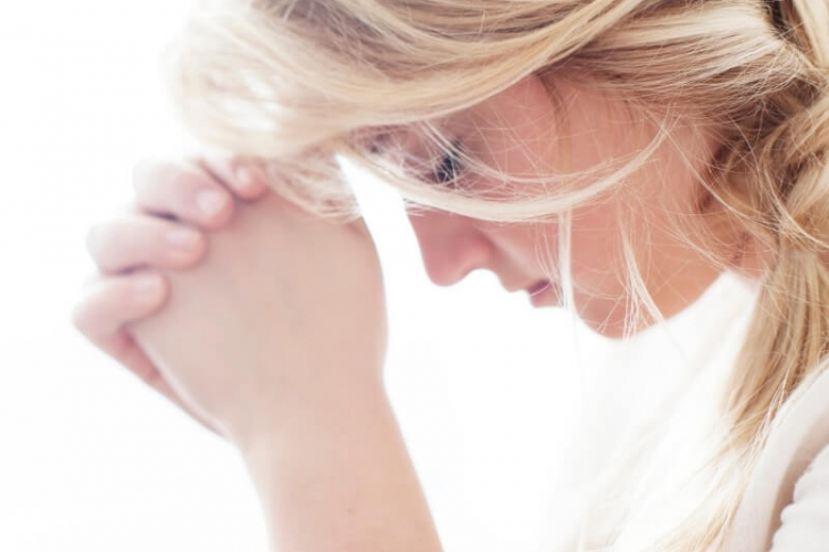 How to Pray when you don't know how. A woman bowing her head in prayer to the Lord